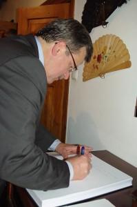 Prezydent wpisuje się do księgi pamiątkowej muzeum